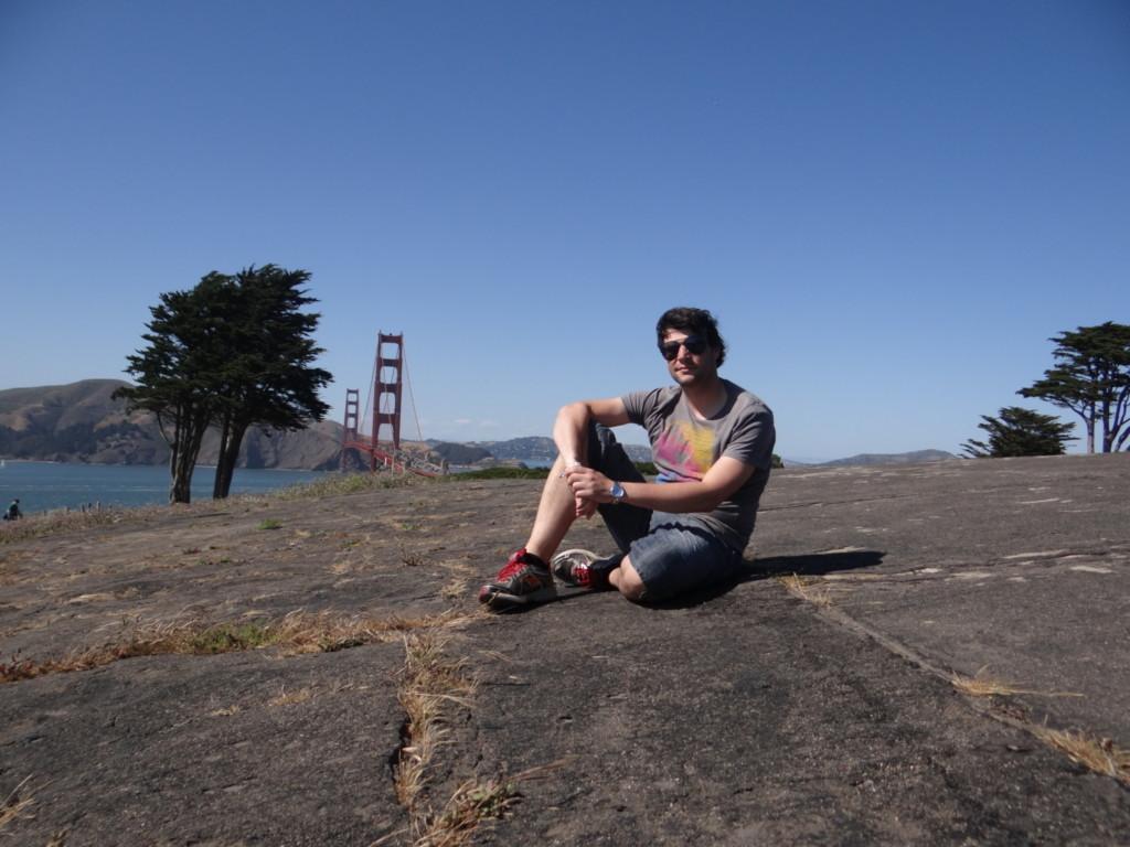 Christian Winter sitzt auf dem Boden. Im Hintergrund erstreckt sich der Himmel und linke hinter ihm die Golden-Bridge.