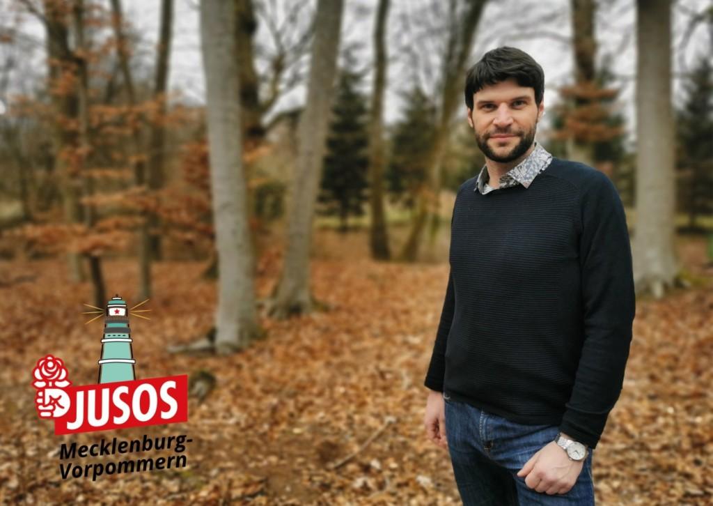 Christian Winter steht in einem Wald. Links unten ist das Logo der Jusos Mecklenburg-Vorpommern zu sehen.