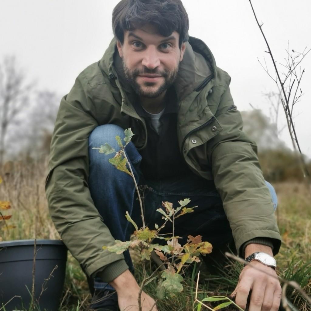 Christian Winter pflanzt einen kleinen Baum ein.