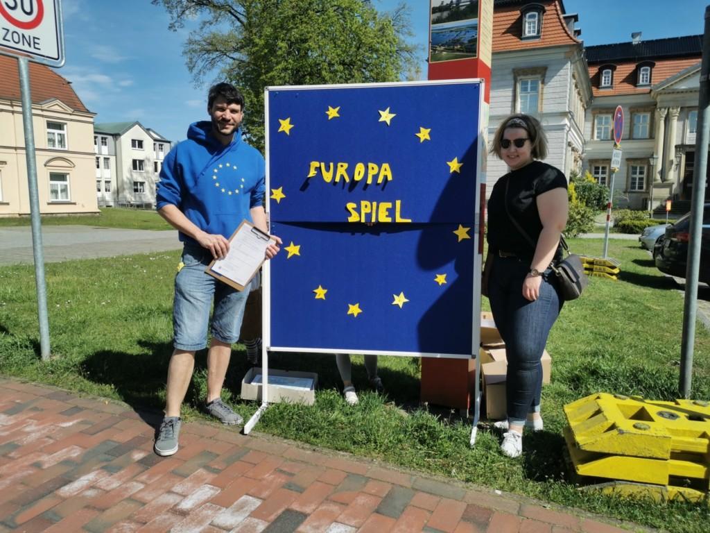 """Vor dem Neustädter Schloß sind Christian Winter und Team vor einer Pinnwand mit der Aufschrift """"Europaspiel"""" zu sehen."""