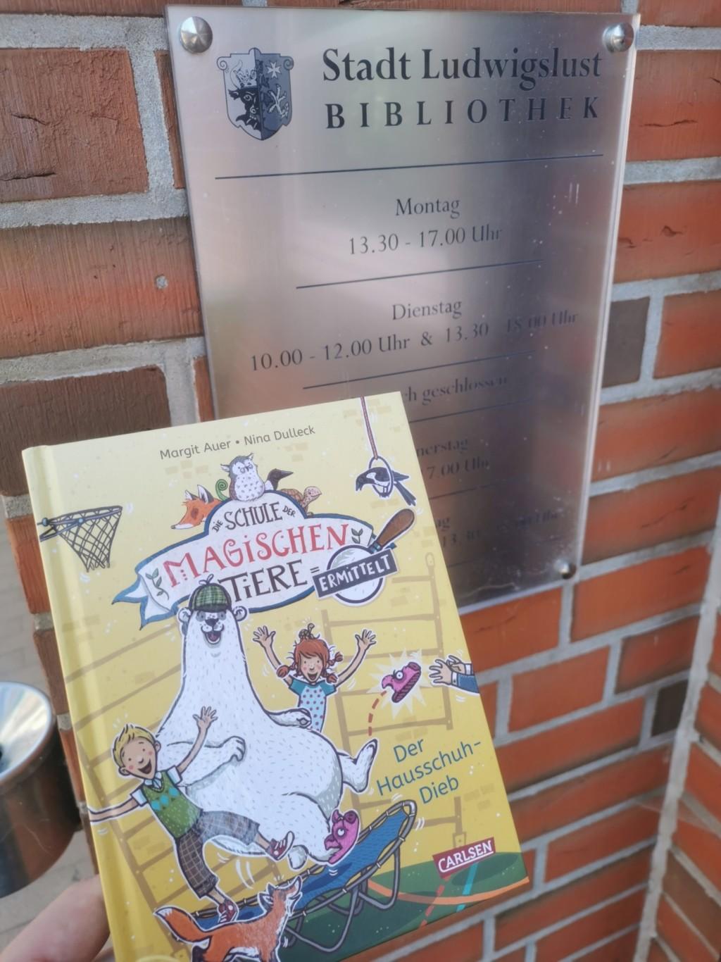 """Das gespendete Buch """"Schule der magischen Tiere-Der Hausschuhdieb wird vor dem Eingangsschild der Bibliothek präsentiert."""