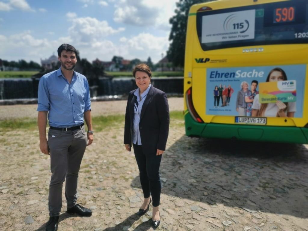 Christian Winter und Landessozialministerin Stefanie Drese stehen vor dem Kaskadenbrunnen in Ludwigslust. Rechts im Bild steht ein Bus, auf dessen Rückseite für die Ehrenamtskarte geworben wird.