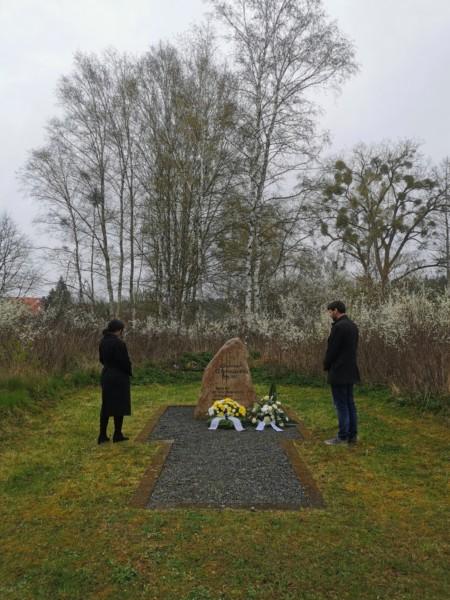Am Gedenkstein des Konzentrationslagers stehen links Reem Alabali-Radovan und rechts Christian Winter in Gedenkhaltung, nachdem sie ein Gesteck niederlegten.