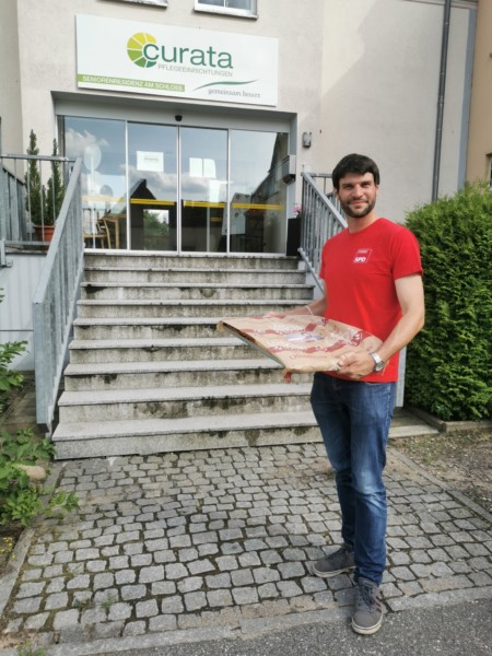 Vor einer Neustädter Pflegeeinrichtung steht Christian Winter, im roten T-Shirt, um ein Blech Kuchen abzugeben.