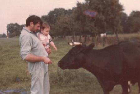 Christian Winter als einjähriges Kind auf dem Arm seines Vaters gegenüber einem schwarzen Rind.