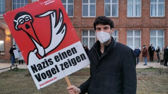 """Christian Winter steht mit einem Schild """"Nazis den Vogel zeigen"""" von Stroch Heinar vor dem Zebef in Ludwigslust."""