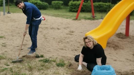 Doreen Radelow und Christian Winter durchforsten den Sand am Spielplatz in der Zeppelinstraße nach Unkraut und Unrat.