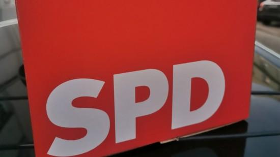 Ein Würfel mit der Aufschrift SPD steht auf schwarzem Grund unter freiem Himmel.