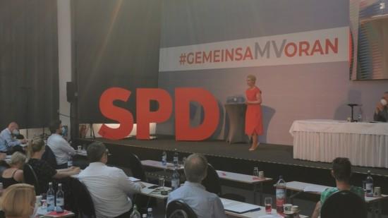 Auf der Bühne der Versammlung ist Manuela Schwesig während einer Rede zu sehen. Sie steht nebendrei großen Buchstaben, die SPD zeigen, und unter dem Slogan #GemeinsaMVoran.