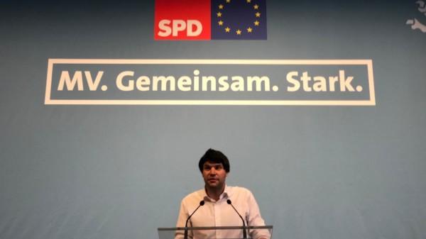 """Christian Winter steht an einem Redepult, vor blauen Hintergrund, auf dem das SPD-Logo und die Europa-Flagge mit dem Schriftzug """"MV. Gemeinsam. Stark."""" zu lesen ist."""