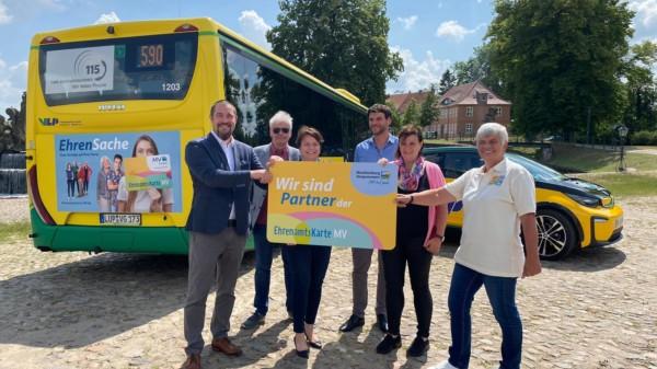 """Sechs Personen stehen vor einem Bus und einem E-Fahrzeug auf dem Ludwigsluster Schloßplatz und halten eine große Karte mit der Aufschrift """"Wir sind Partner"""" hoch."""