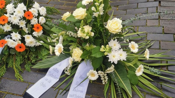 Auf dem Gedenkplatz des ehemaligen Lagergeländes des KZ Wöbbelin liegt ein Gesteck, mit dem Reem Alabal-Radovan und Chrisian Winter der Opfer gedenken.